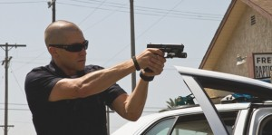 Brian (Jake Gyllenhaal) takes aim at a suspect in End of Watch